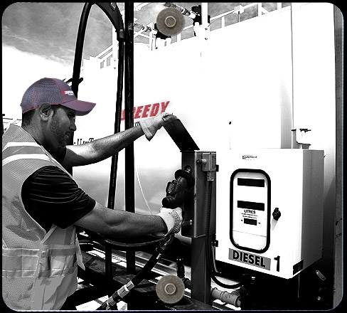 Speedy transport driver refueling truck before shipping